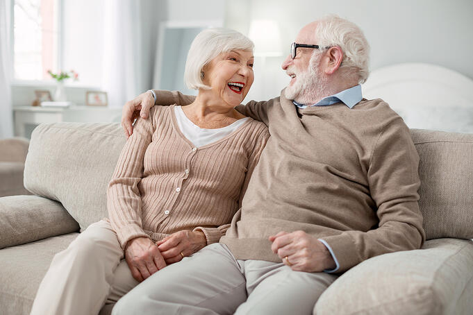 Senior couple create new year resolutions together while sitting on a couch.