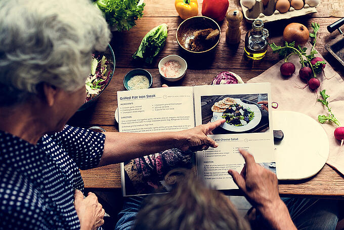 Senior woman points to a healthy winter recipe to make for dinner.