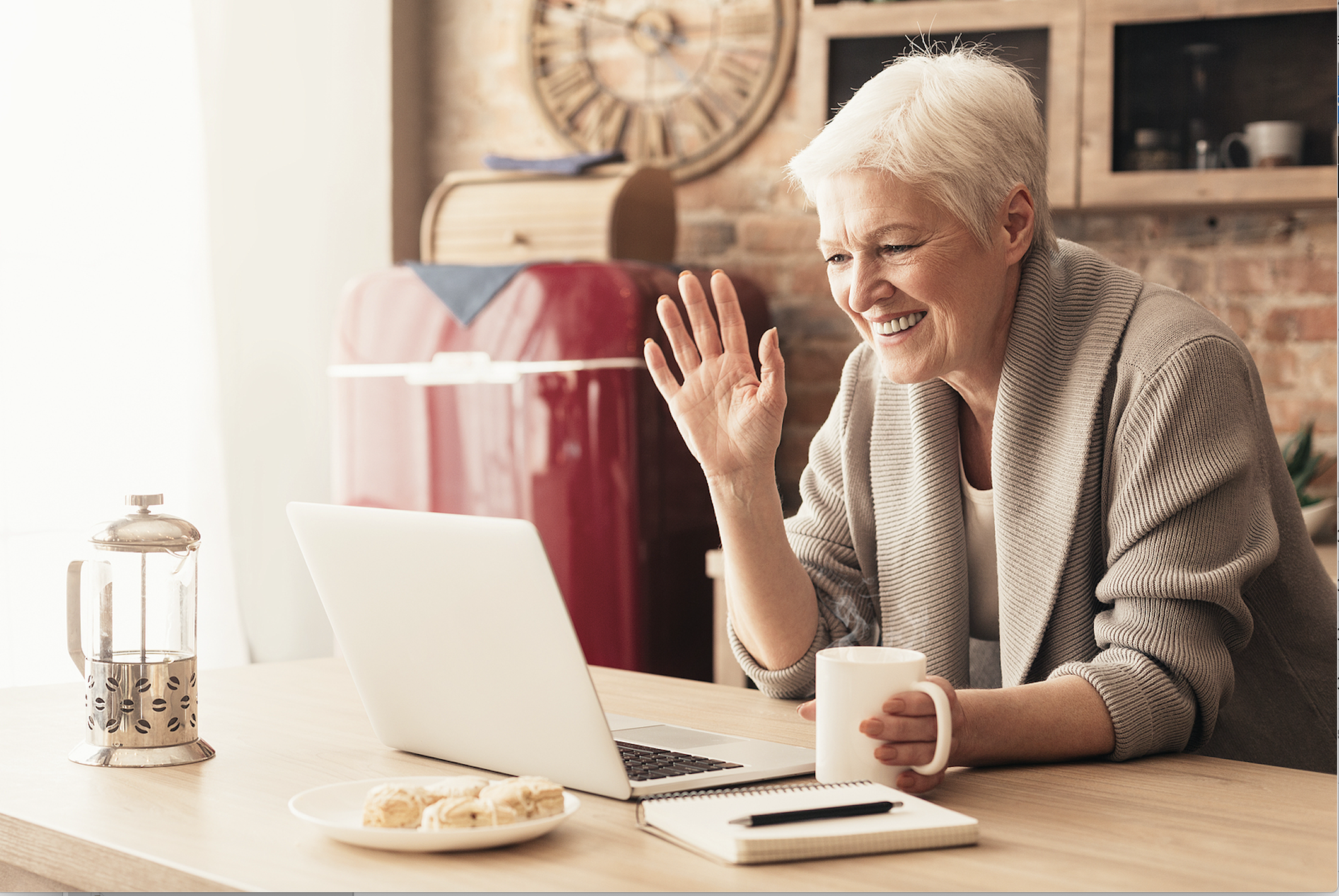 Happy senior woman visits virtually with loved ones.